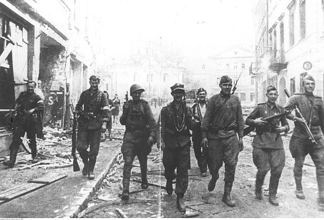 Red Army and Polish resistance troops walk together down a street