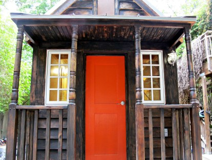 Front porch with orange-red door and dark siding.