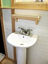 Pedestal bathroom sink and faux brick wall.