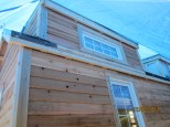 A dormer with all of the siding up.