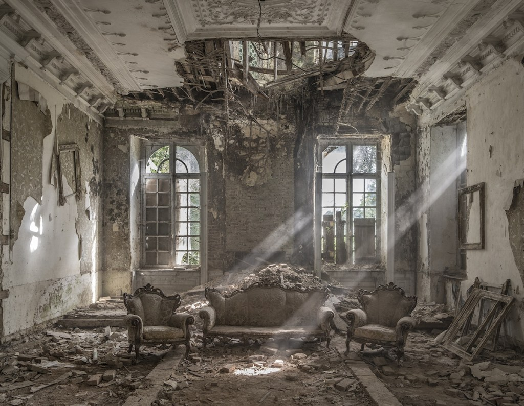 mostly monochrome photo of the interior of a ruined chateau, with dramatic sunbeams illuminating part of it