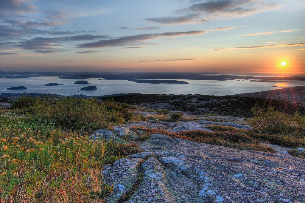 photo of a sunrise over a landscape of rocks, lichen, wildflowers, and still water