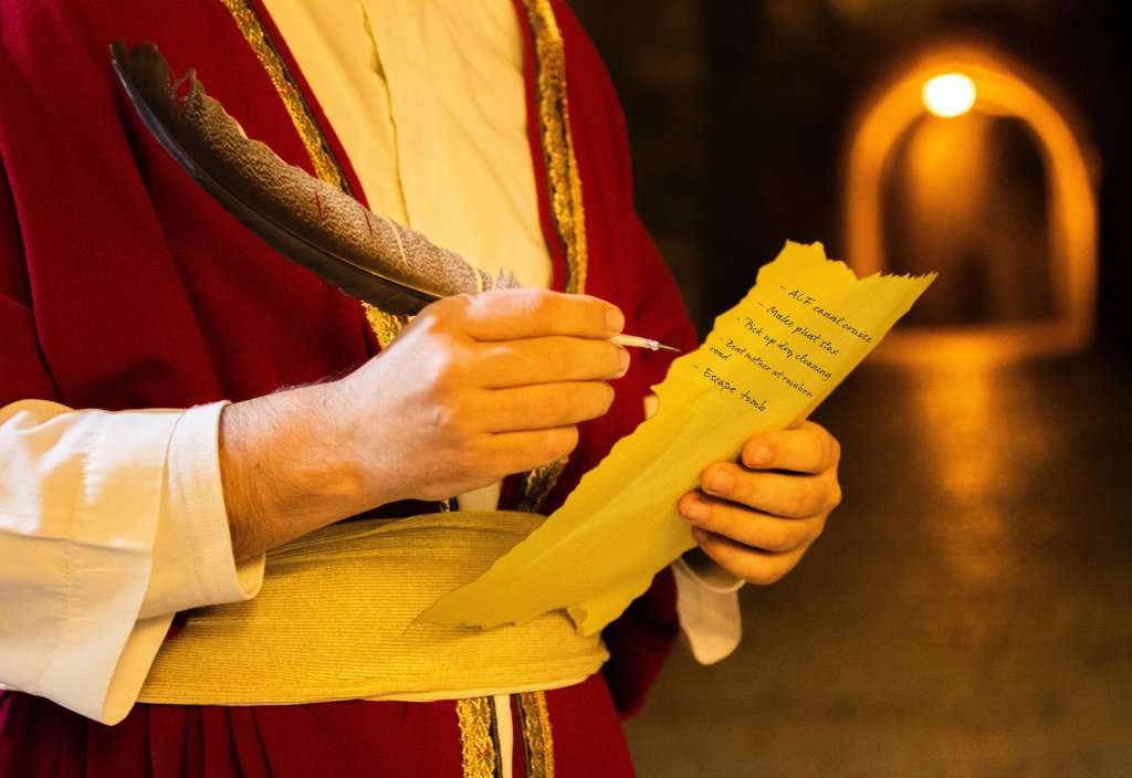 A male holds a quill and a piece of parchment with a list written on it inside of a tomb