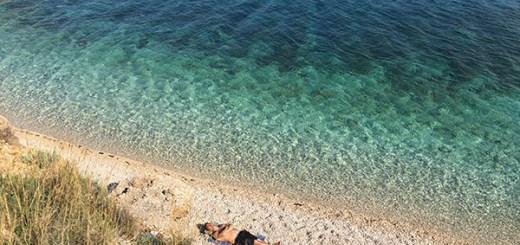 homem dormindo em praia deserta com águas cristalinas em hvar, na croácia