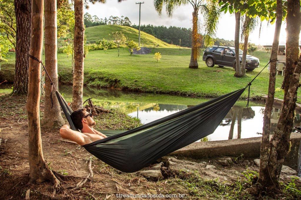 rapaz deitado e relaxando em uma rede na beira do rio, no camping e cachoeira paulista, em dr pedrinho