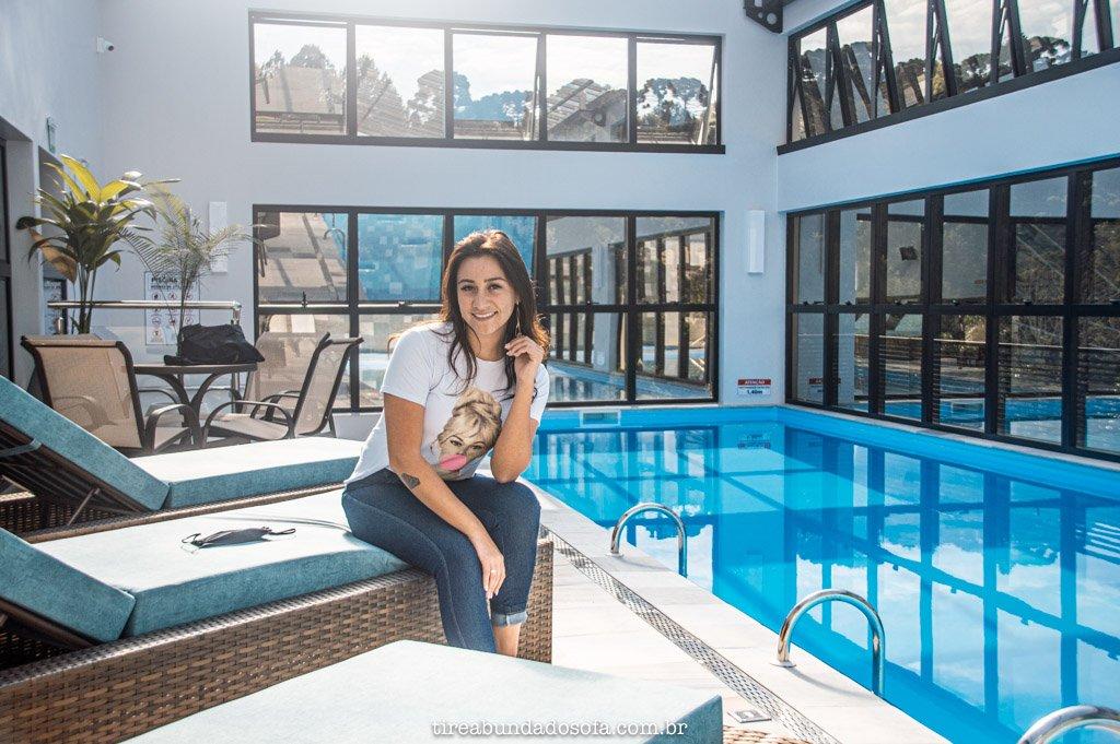mulher sentada em espreguiçadeira, na área da piscina aquecida no lefel hotel. Piscina no terraço.