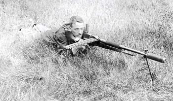 """Maxim dispara con un fusil automático Benét-Mercié M1909 que lleva montado uno de sus supresores. Foto de la revista """"Small Arms Review"""" [Revista de Armas Portátiles]"""