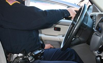 Se abre la puerta al tiempo que se lleva la pistola a la posición de las nueve al lado del volante y se empieza a salir del coche.