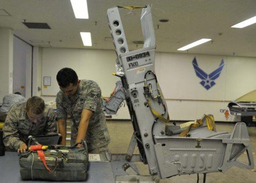 El Soldado Peter Curry y el Cabo Jeffrey Bowen,aprendiz y técnico, respectivamente, de sistemas de escape de tripulacionesdel 35º Escuadrón de Mantenimiento del Ejército del Aire estadounidense, consultan una instrucción técnica sobre la instalación de un kit de supervivencia de tripulaciones en la Base Aérea de Misawa, en Japón, el 31 de julio de 2014. Una vez que el equipo de escape recibe el kit de supervivencia de manos de la Sección de Equipo de Vuelo de Tripulaciones, lo instalan en el asiento eyectable de un F16 Fighting Falcon (Foto del Ejército del Aire estadounidense/Soldado Patrick S. Ciccarone).