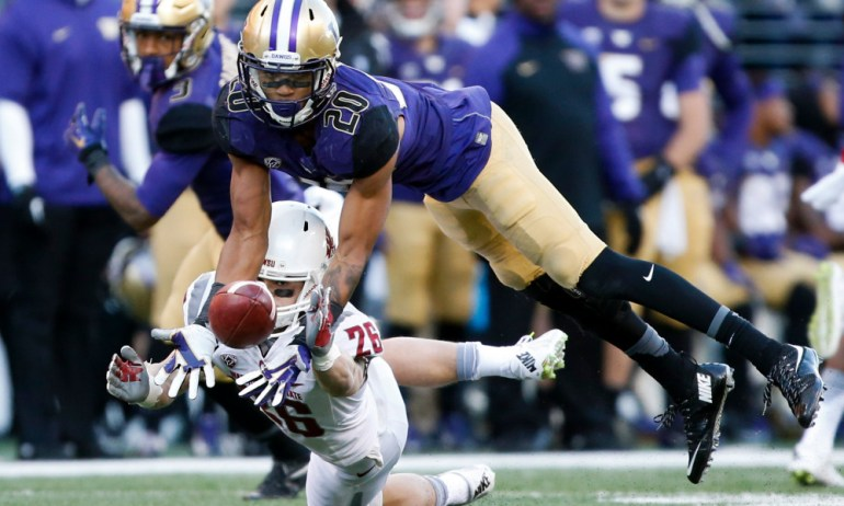 Nov 27, 2015; Seattle, WA, USA; Washington Huskies defensive back Kevin King (20) almost intercepts a pass intended for Washington State Cougars wide receiver Tyler Baker (26) during the fourth quarter at Husky Stadium. Washington beat Washington State 45-10. Mandatory Credit: Jennifer Buchanan-USA TODAY Sports