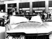 Boxer Cassius Clay, upper left, returns from the Olympics to Louisville, as he rides in a convertible that's turning onto 4th Street from Broadway, Sept. 9, 1960. He was a shy, well-mannered kid who babysat for neighbors and shadow-boxed with the cigar tree in the front yard of his childhood home. And even when Clay won the heavyweight championship, changed his name to Muhammad Ali and became one of the world's most recognized figures, close friends saidhe never lost his bond to the west Louisville neighborhood where he grew up. (AP Photo/The Courier Journal, Al Hixenbaugh)