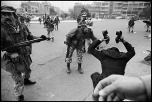 IRAN. Tehran. 1978. A rioter brandishes the shoes of a dead comrade, killed by Army gunfire. The soldier argues that it was not his unit which opened fire.