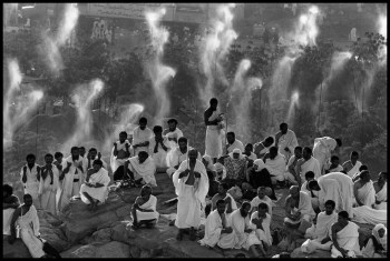 SAUDI ARABIA. Mecca. 1992. Hajj pilgrimage. Pilgrims from all over the world pray on Mount Rahma. Mount Rahma, in the plain of Arafat (where Muslims believe Adam met Eve). Pilgrims dressed in the Ihram (two pieces of unstitched white cloth), gather to show their respect for all forms of life. Driplets of water cool off pilgrims and trees from the dense heat.