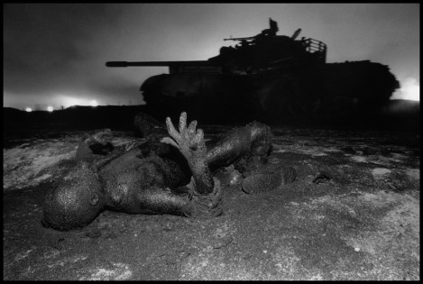 KUWAIT. Next to a tank destroyed by US aerial bombing, a dead Iraqi soldier is mumified by drops of oil escaping from wells, set on fire by the soldier's unit before it retreated.