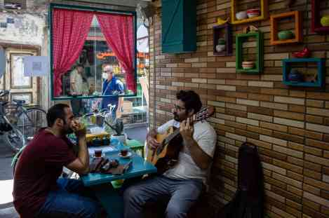Rasht , Iran – May 202. Afraz and Erfan living in Rasht, were introduced to each other by a mutual friend in 2016. Before they met one another, each had been separately playing professionally their own musical instrument. Considering that both of them were musicians, their friendship has soon deepened and after one year of a strong bond they decided to form a band and give street performances in order to earn a wage. Given the country they live in being Islamic, morality police officers have caused them endless trouble ever since they began playing. Though being arrested several times and also had their instruments confiscated each time, they have never given up playing music as indeed it is their only way to make money, no matter how hard it could be in such an Islamic country. Since coronavirus outbreak, these two have been in quarantine as other Iranians have and faced financial difficulties consequently. Nevertheless, as the situation getting better they have started to work again while following safety protocols but earning less considerably than before. With regard to being highly celebrated in the city, in addition to perform street performances, Afraz and Erfan have been playing as surprise guests at birthday parties in return for a small sum of money since a while ago. To updated their tunes, Afraz and Erfan do practices at various places, one of which is a café belonging to Mahzad, an old friend of Erfan.