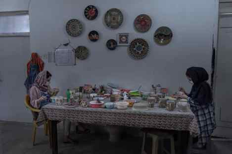 Gorgan, Iran-JUN 2020: Maedeh and Nazanin are painting potteries by observing the social distance.Iran was amongst five of the countries with the highest spread of COVID-19. Iran's government began an official lockdown on March 15th, 2020, the quarantines in place are for those who do not exhibit symptoms but have been exposed to the illness. For the large number of Iranians who live on a day by day income, staying home, means having no money to pay for essential things such as food. Therefore, they must take their life in their own hands and work in order to survive even at the risk of getting infected, spreading the virus in society at large, and even getting fined for breaking the quarantine. For them, choosing either path has extreme consequences. (Photo by Kianoush Saadati/NVP Images)
