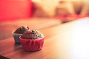 Two muffins with candy toppings on a table