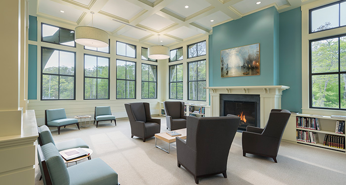 A seating area of the library that has many large chairs in front of a fireplace with a painting hanging over it