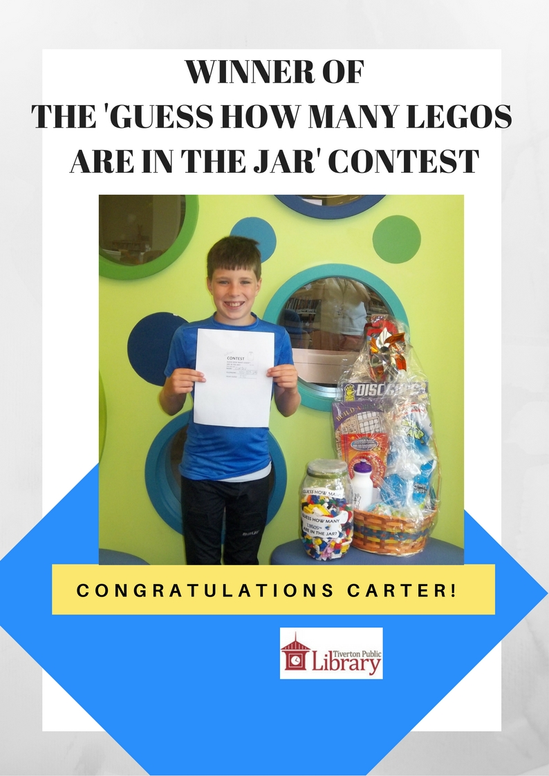 Photo of a boy named Carter holding a paper and standing next to a gift basket he won for guessing the amount of legos in a jar