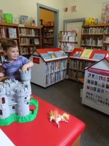 A child playing with a toy castle in front of the children's books shelves