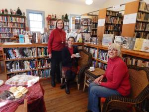 photo of three woman sitting and standing with one holding a teacup inside the union library