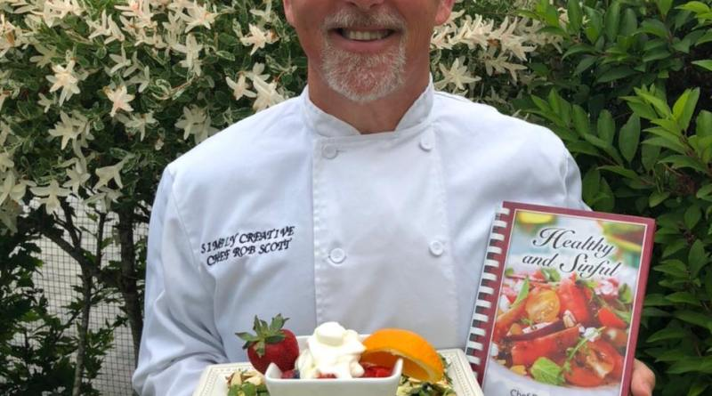 rob scott chef with food on a plate and a book in hand