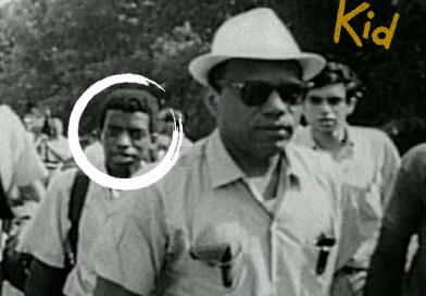 the civil rights kid. several people walking in the street. a young black man is circled in the photo