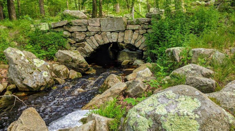 arched_bridge_weetamoo water stream rocks around it a stone bridge over the stream