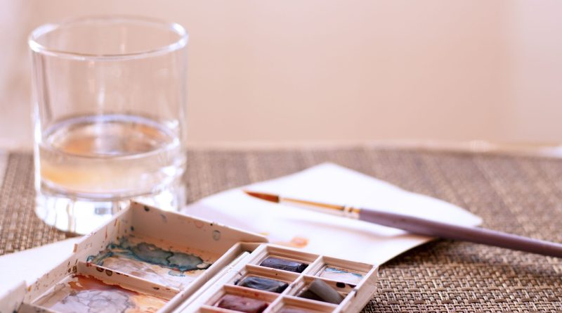 watercolor paint water and brush supplies on the table