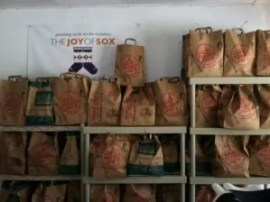 Lots of bags of sorted socks waiting to be delivered to the homeless by The Joy of Sox.