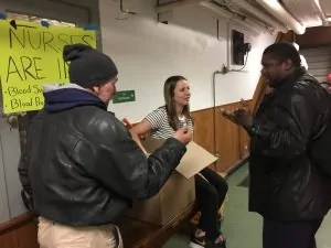 Handing out news socks to the homeless at Grace Cafe, Arch Street Methodist Church, Philadelphia, PA. Eliza Clark, an intern from Villanova University for The Joy of Sox, a nonprofit that gives joy to the homeless by giving them new socks, talks with two homeless men.