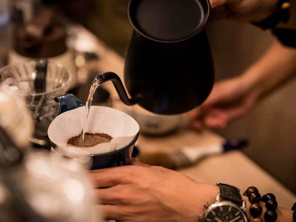 有一雙手拿著茶壺正在沖咖啡,一道水柱正注入咖啡粉中