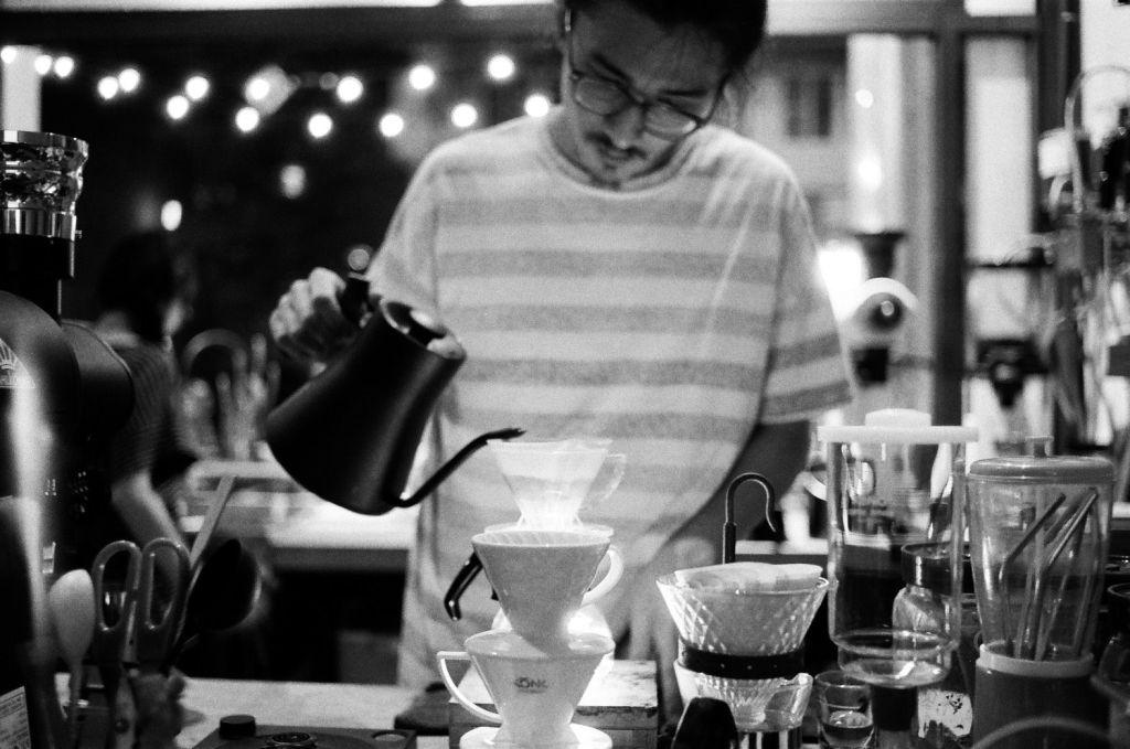 黑白照片,有個戴眼鏡穿條紋衣的男人拿著茶壺正在沖咖啡