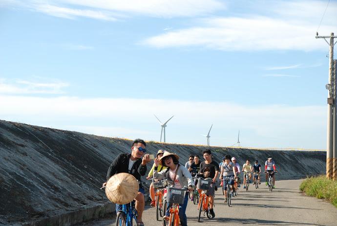 有很多人在堤防邊騎腳踏車戴著斗笠,後面還有風力發電