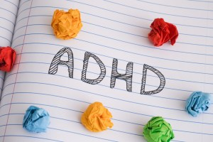 ADHD on notebook sheet with some colorful crumpled paper balls on it