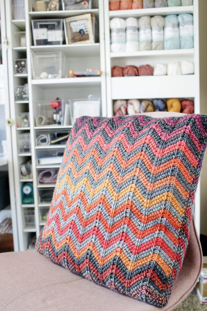 Make the Easy Ripple Pillow, a free Tunisian crochet cushion pattern using a unique chevron pattern. Watch the included tutorial video to learn this stitch from start to finish. | TLYCBlog.com