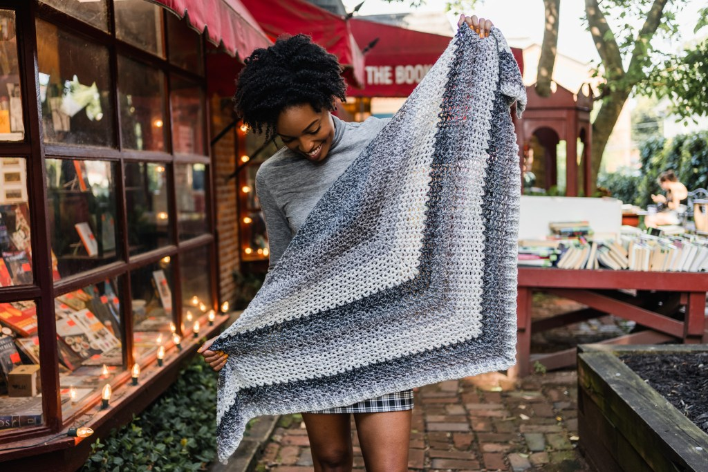 Learn to crochet this easy beginner crochet triangle scarf. The Omar Wrap features crochet v-stitches, ribbing, and color changing cake yarn.
