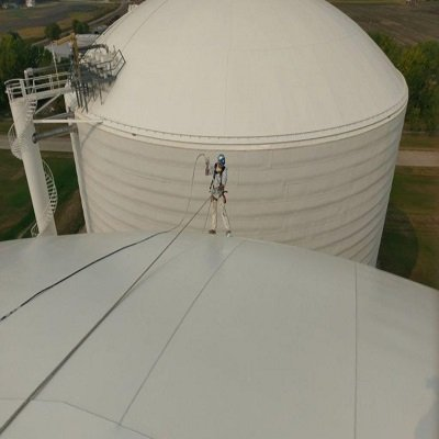TMI Coatings worker painting the side of an ammonia tank.