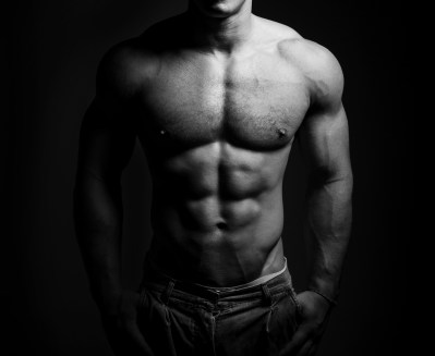 bodybuilder posing. Handsome power athletic guy male. Fitness muscular body on black background. Black and white photo