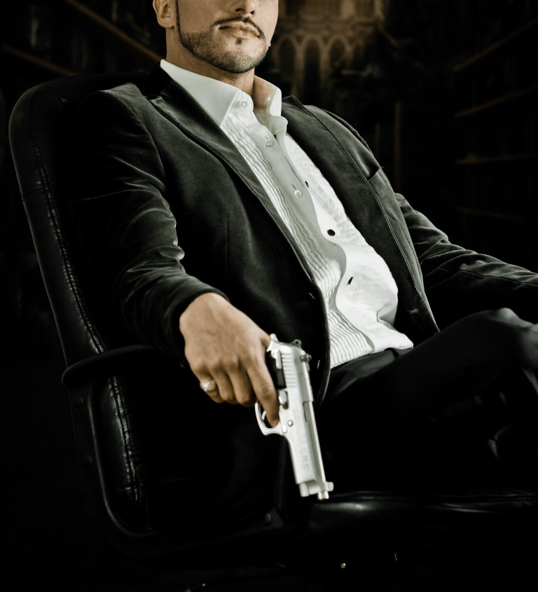 Elegant man sitting in a chair holding  gun over dark background