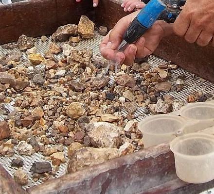 רשת סינון עם אבנים מהעפר למיון וצינור מים