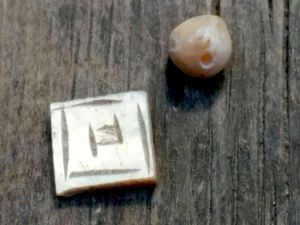 חרוז ושיבוץ מעוטר חריתה עשוים מאם הפנינה.