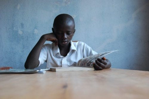 A boy reads a book in the new Community Learning Centre in UVira