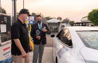 Driver Wayne Gerdes and GUINNESS WORLD RECORDS adjudicator Michael Empric inspect sealed hydrogen fuel opening on Mirai