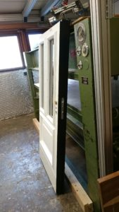 Ytterdörr vit och svartmålad med två glas och en spegel