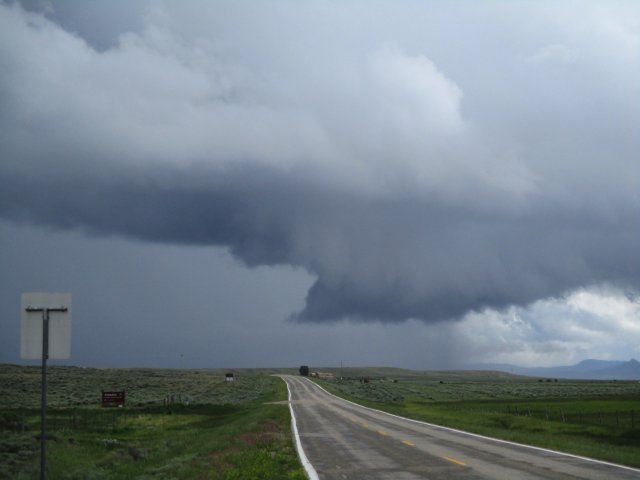 A storm over an open valley in Colorado. There is a could that looks like a nascent tornado.