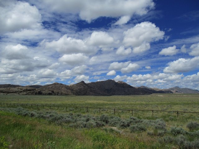 Fluffy clouds in a blue sky over a plain with granite mountains in the background.