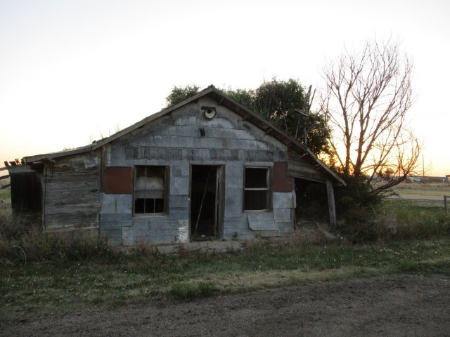 A small dilapidated one-story building with the sun setting in the background.