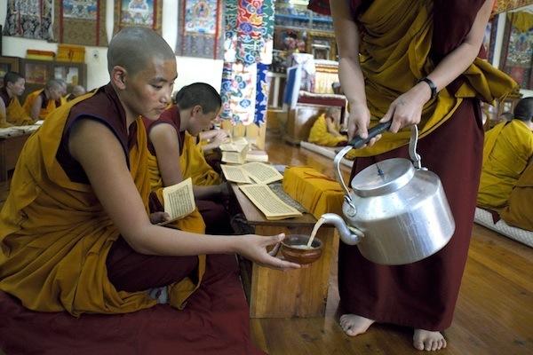 nun pouring tea in prayer hall Geden Choeling Nunnery