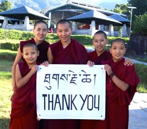 5 Tibetan Buddhist nuns hold a thank you sign in Tibetan and English